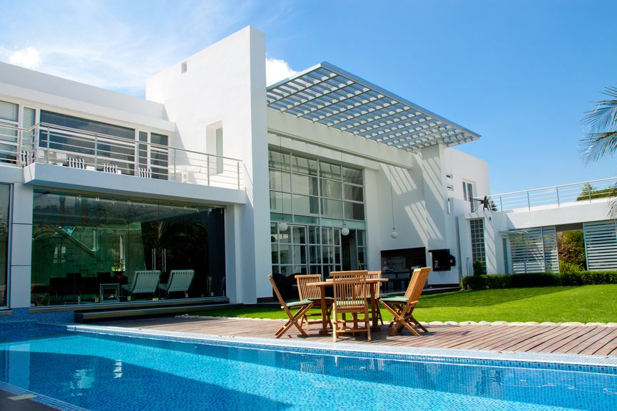 2 story white home with long rectangle pool bordered by wooden deck and grass - Rectangle Pool Aerial View