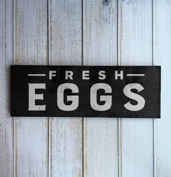 """Our """"Fresh Eggs"""" sign is an absolute farmhouse classic. Sit it on a shelf amongst kitchen items or hang it on the wall. Measures 3.5"""" x 9.25"""". White ink on soft black. Most of our signs are made to or"""