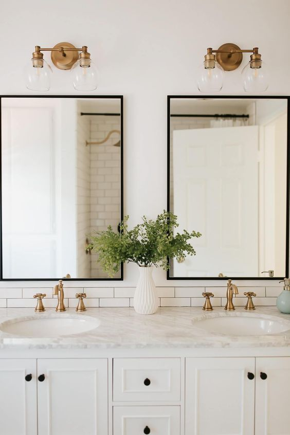 All white double sink bathroom with marble countertop and golden lamps and faucets
