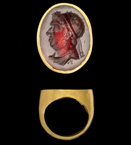 A HELLENISTIC GOLD AND GARNET INTAGLIO RING WITH ROYAL PORTRAIT OF A PTOLEMAIC RULER, PROBABLY PTOLEMY IX, SOTER II. LATE 2ND/EARLY 1ST CENTURY B.C.