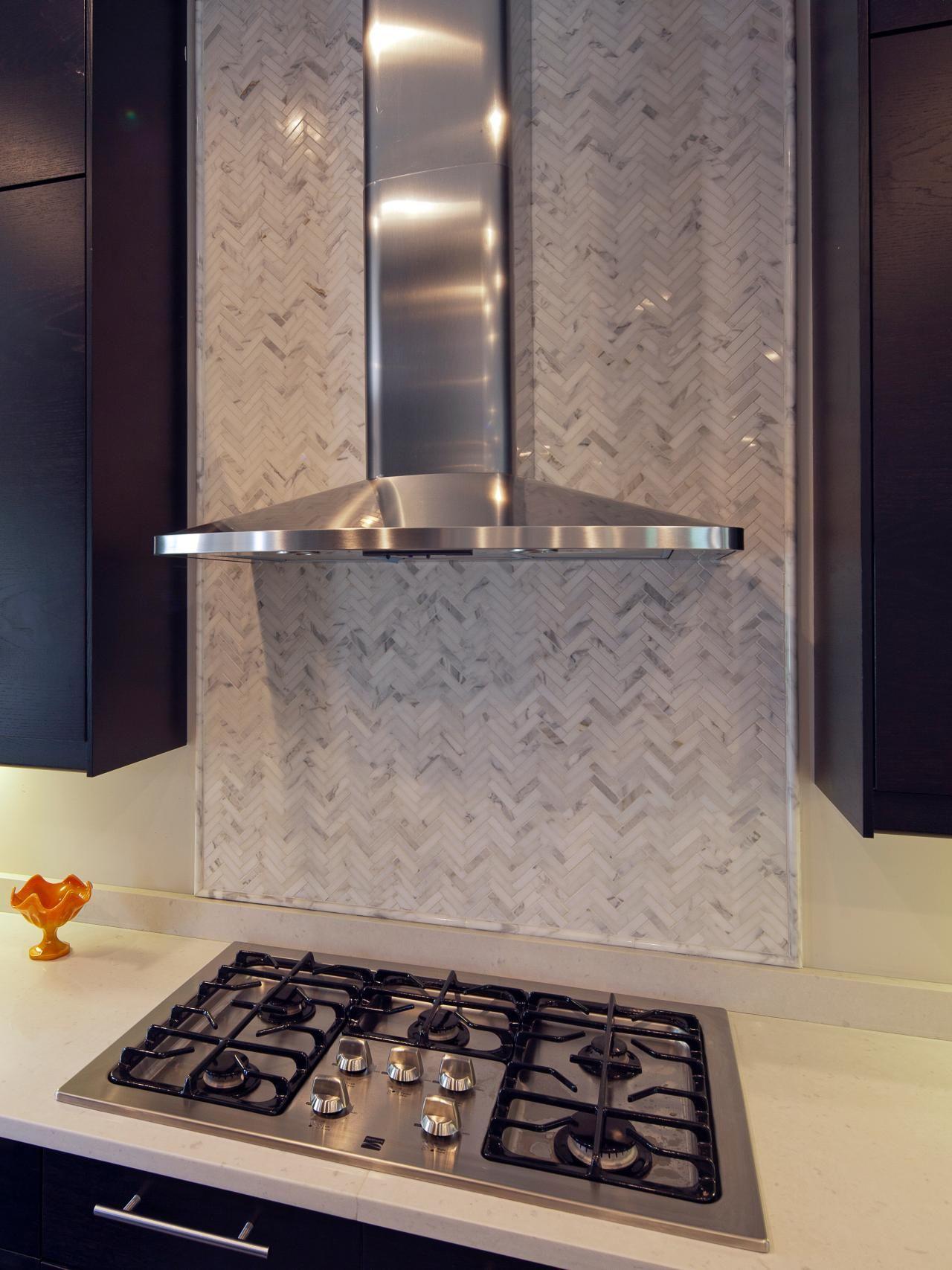 Limestone tiles layered in a herringbone pattern create a focal limestone tiles layered in a herringbone pattern create a focal point behind the range hood dailygadgetfo Gallery