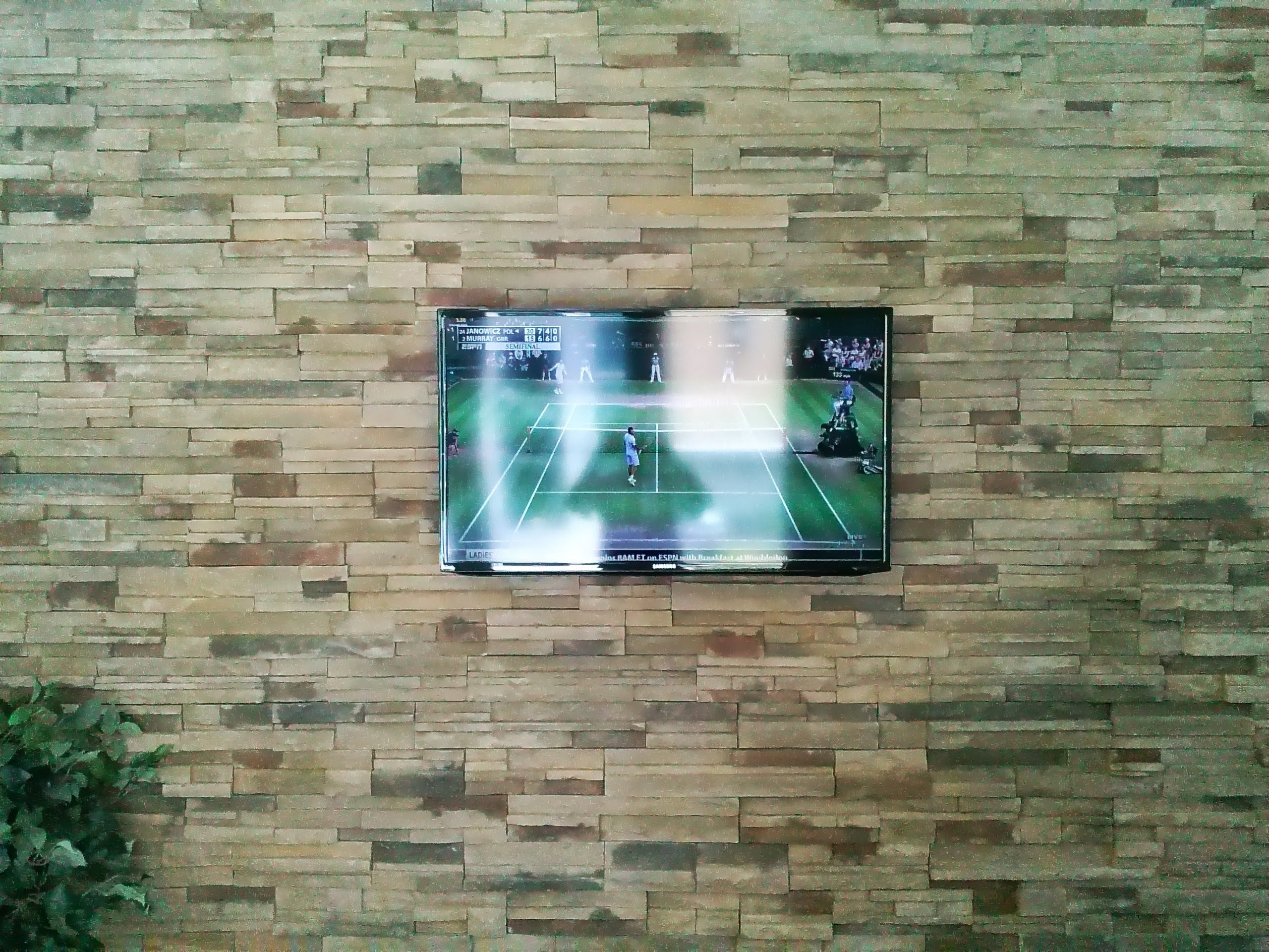 TV installation on sandstone wall with the wires concealed in the ...