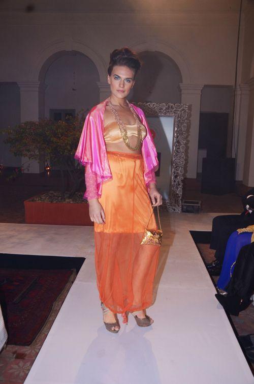 Pink shot-silk draped jacket, copper satin bustier and dusk orange net blouson-skirt. INR 5,290