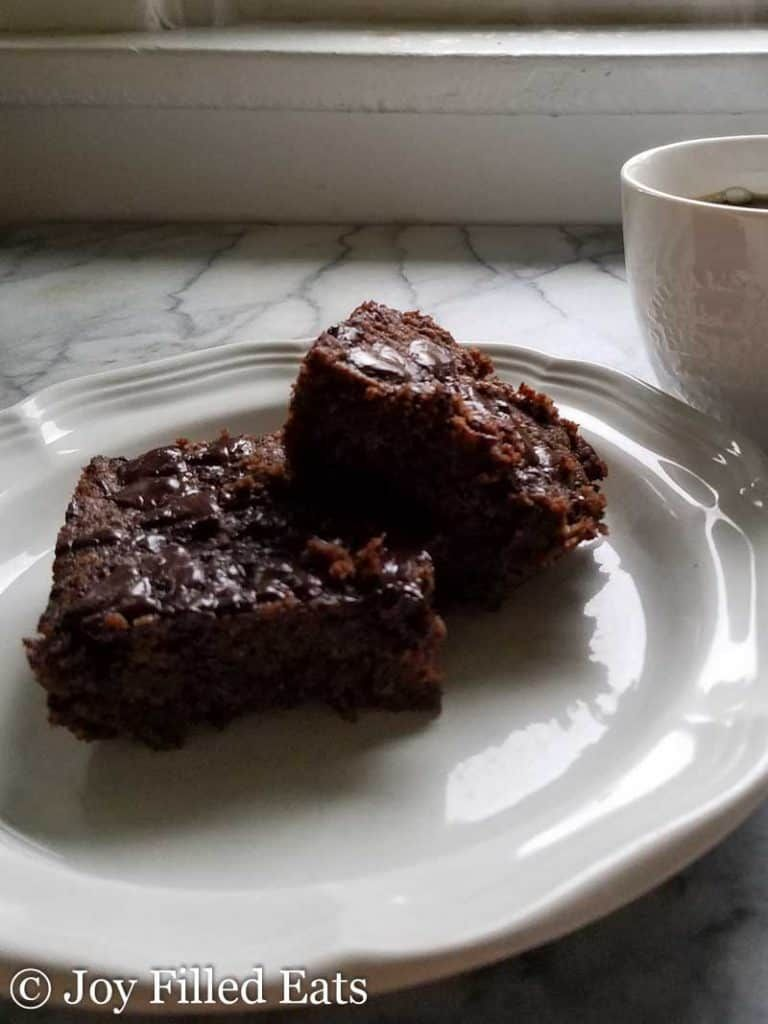 Brownies Stacked On A White Plate On A White And Gray Marble