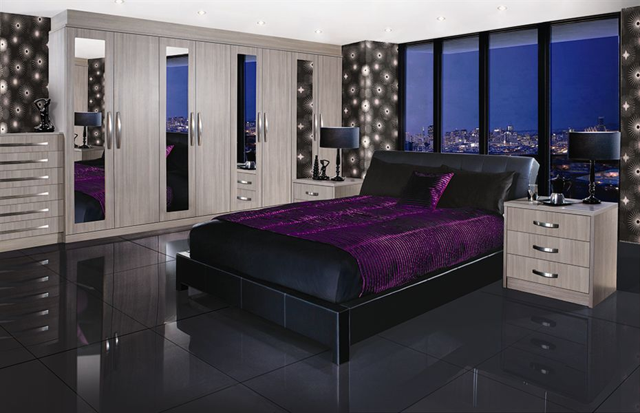 Modern Avola Grey Bedroom - Modern feature wallpaper - Modern large gloss floor tiles - Bedside drawer table cabinets - Ceiling lights - Mirror wardobes | Atlantis Kitchens | Bedrooms