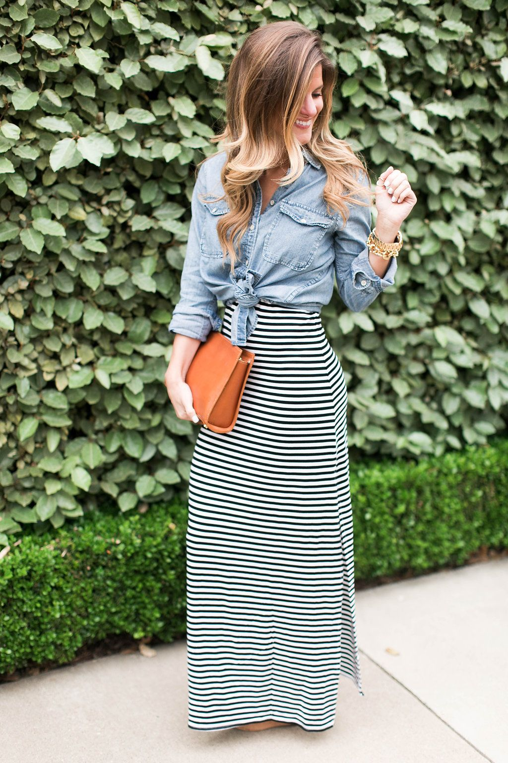 bd972368555 How to Wear a Denim Shirt    13+ ways to style your favorite denim shirt     striped maxi dress + chambray shirt on top tied up + gigi NY Cognac leather  ...