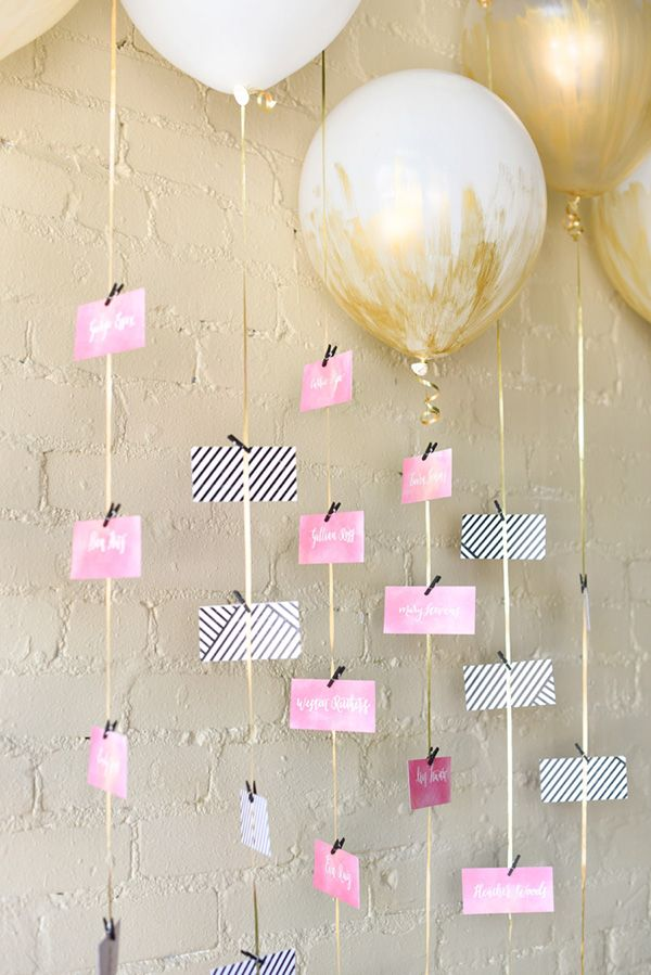gold balloon wedding seating chart with escort cards hanging from the strings