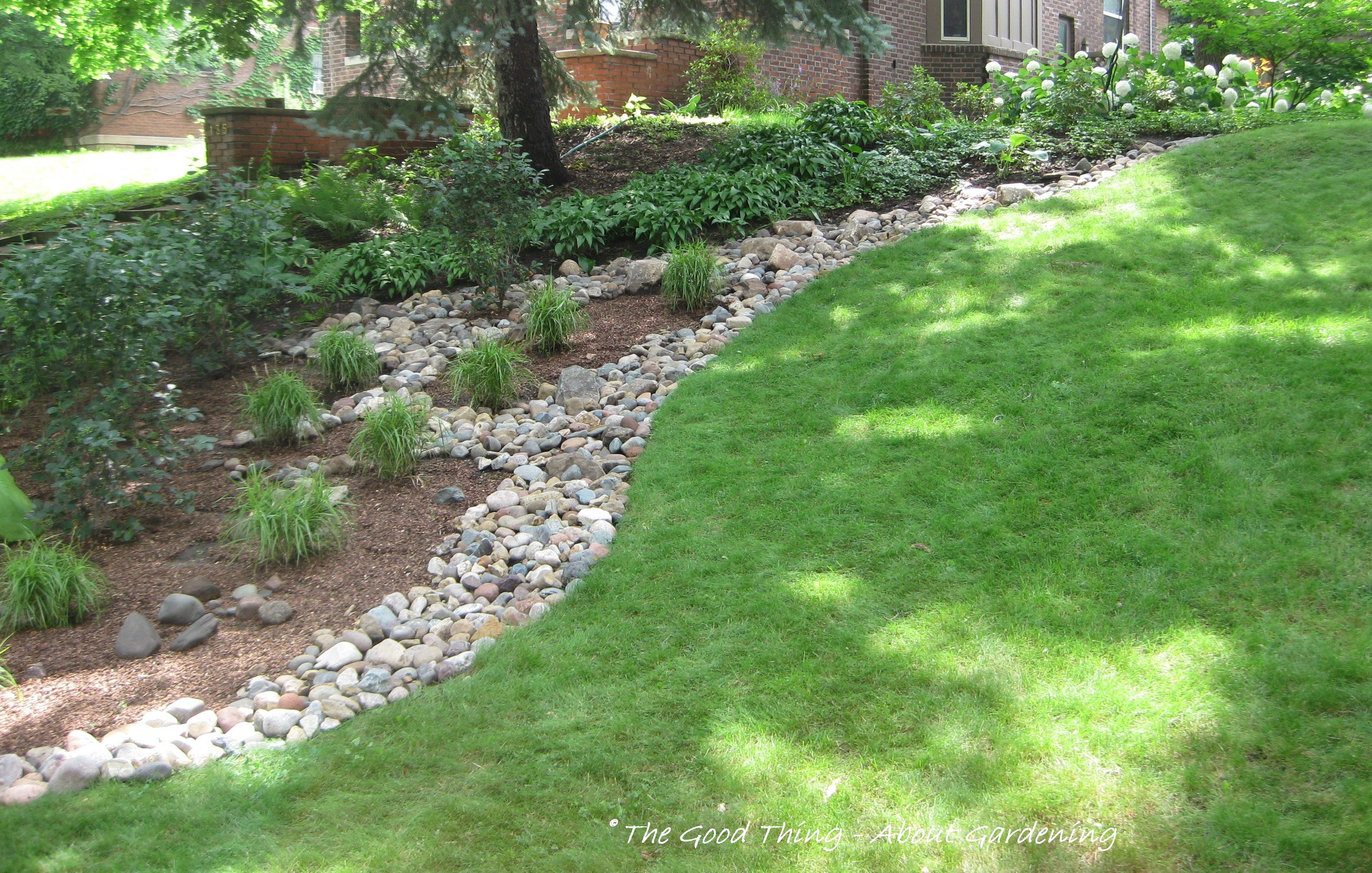 River rock as a divider between the grass and plant beds for Dry garden designs