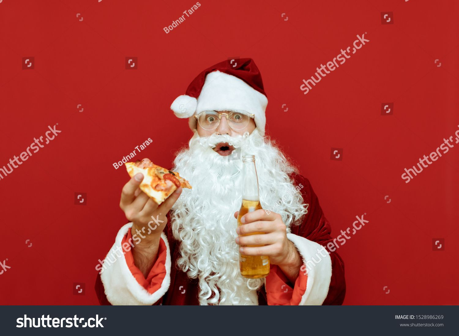 Surprised Santa Claus With Piece Of Pizza And Bottle Of Beer In Hand Stands On Red Background Looks Into Camera With Sh In 2020 Santa Funny Santa Claus Piece Of Pizza