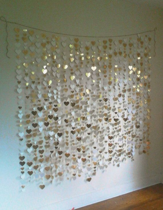 Gold Heart Backdrop  -----------------  SPECS: *16 strands of handmade garland hang from jute rope. Dimensions: choose a dimension from the drop-down menu or message us for custom dimensions. An additional 2 ft of rope on each end is included for hanging. *Heart size: mix of 1 inch and 2.5 inch *Each heart is punched by hand from metallic gold foil cardstock and sewn together. Hearts are white on one side and gold on the other.  colors and shapes and dimensions are all completely…