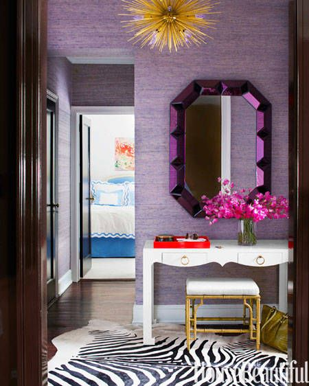 n this Manhattan apartment's entry, a Romano mirror from Bungalow 5 picks up the purple in Phillip Jeffries's Juicy Jute grass cloth on the walls. Jacqui desk and Collette stool from Bungalow 5. Zanadoo hanging light by Arteriors. Faux-zebra rug from ABC Carpet & Home. Designed by Lilly Bunn.