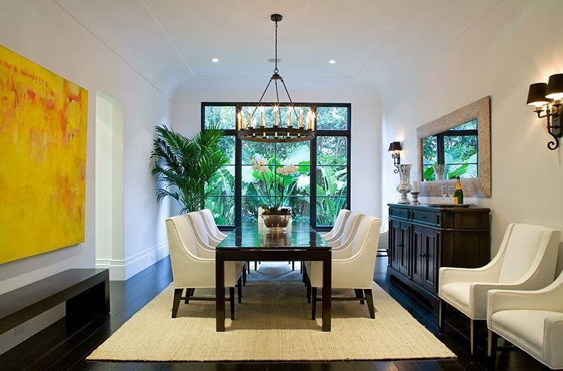 Formal living room in a Spanish revival home with white armchairs
