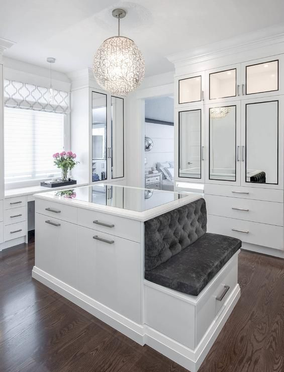 Luxurious Walk In Closet Boasts An Ornate Chandelier Hung Over A Mirror Top  White Center Island Finished With Satin Nickel Pulls And A Built In Bench  Topped ...