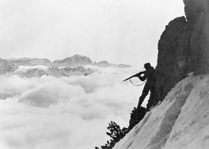 An Austro-Hungarian mountain soldier taking aim with his rifle from a mountain slope while silhouetted against mountain peaks shrouded in clouds.
