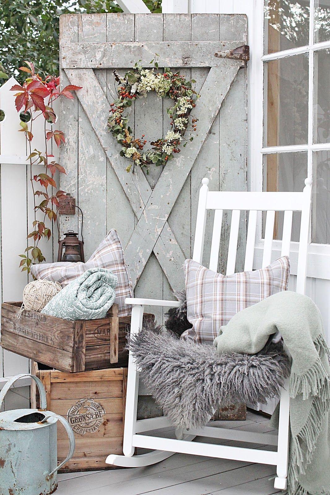 Cozy vignette with a wooden door, wreath, crates, rocking chair ...