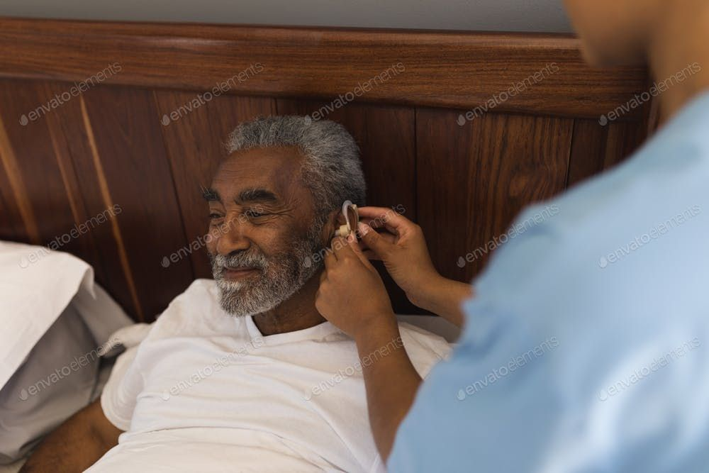 Female doctor fitting senior african american man with