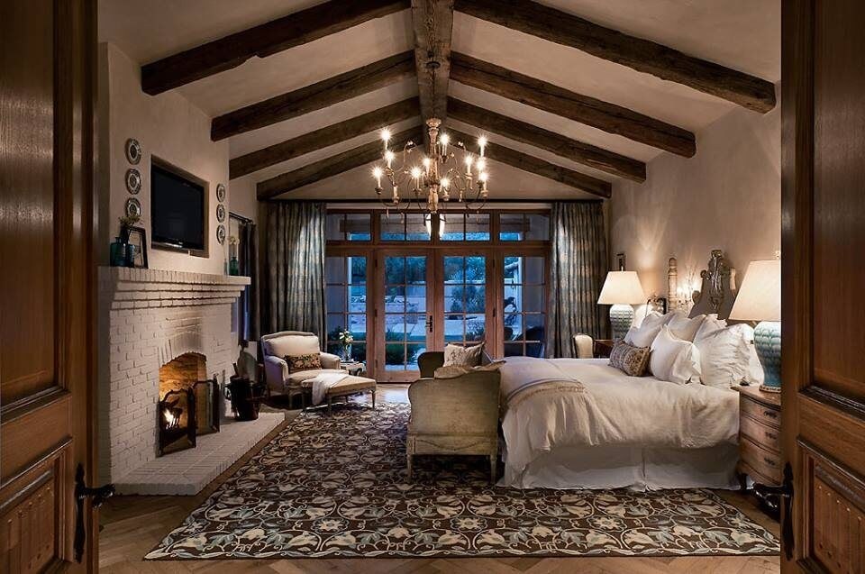 This Luxuriously Decorated Master Bedroom Has A Large White Brick Fireplace.  Exposed Wooden Beams Match