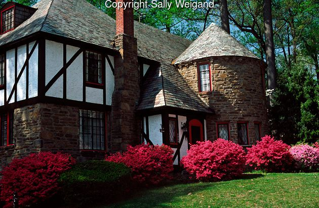 Stone Tudor House tudor house, round turret; stone; stucco; colorful azaleas; spring