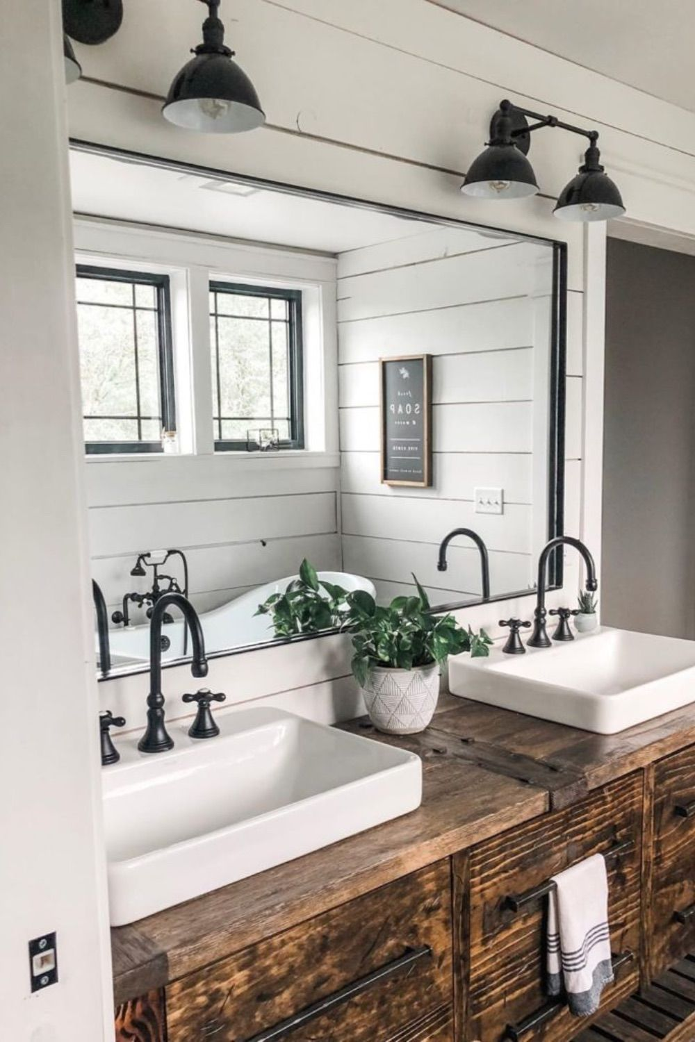 This farmhouse bathroom makes use of shiplap walls with a beautiful rustic bathroom vanity. Two farmhouse lights are used on top of each side of the mirror.