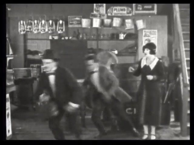 232. The villains race off, as the boss's daughter looks on in surprise. | Fast and Furious (1924)