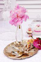Pfingstrosenblüte in Kristallvase mit Besteck auf silbernem Tablett