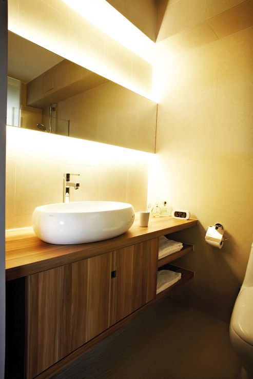 A feeling of luxury is created by mood lighting behind the bathroom ...