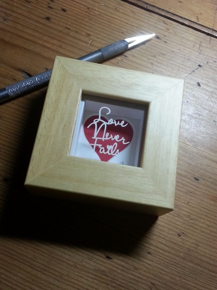 'Love Never Fails' - Miniature Original Papercut This little papercut is cut from a single sheet of cream textured paper, magically floating over a red heart mount casting pretty shadows.