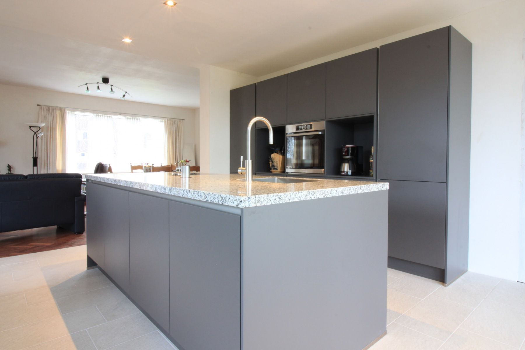 Antraciet muur wit en licht grijs kookeiland wonen en keuken in