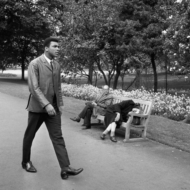 A fresh faced Muhammad Ali (Cassius Clay) walks through a London park the morning after defeating challenger Henry Cooper in the World Title bout at Arsenal's Highbury Stadium. The fight ended with a 6th round stoppage for Muhammad Ali. Two sleepy Londoners (on bench) seems to be anonymous to the presence of the Heavyweight Champion of the World