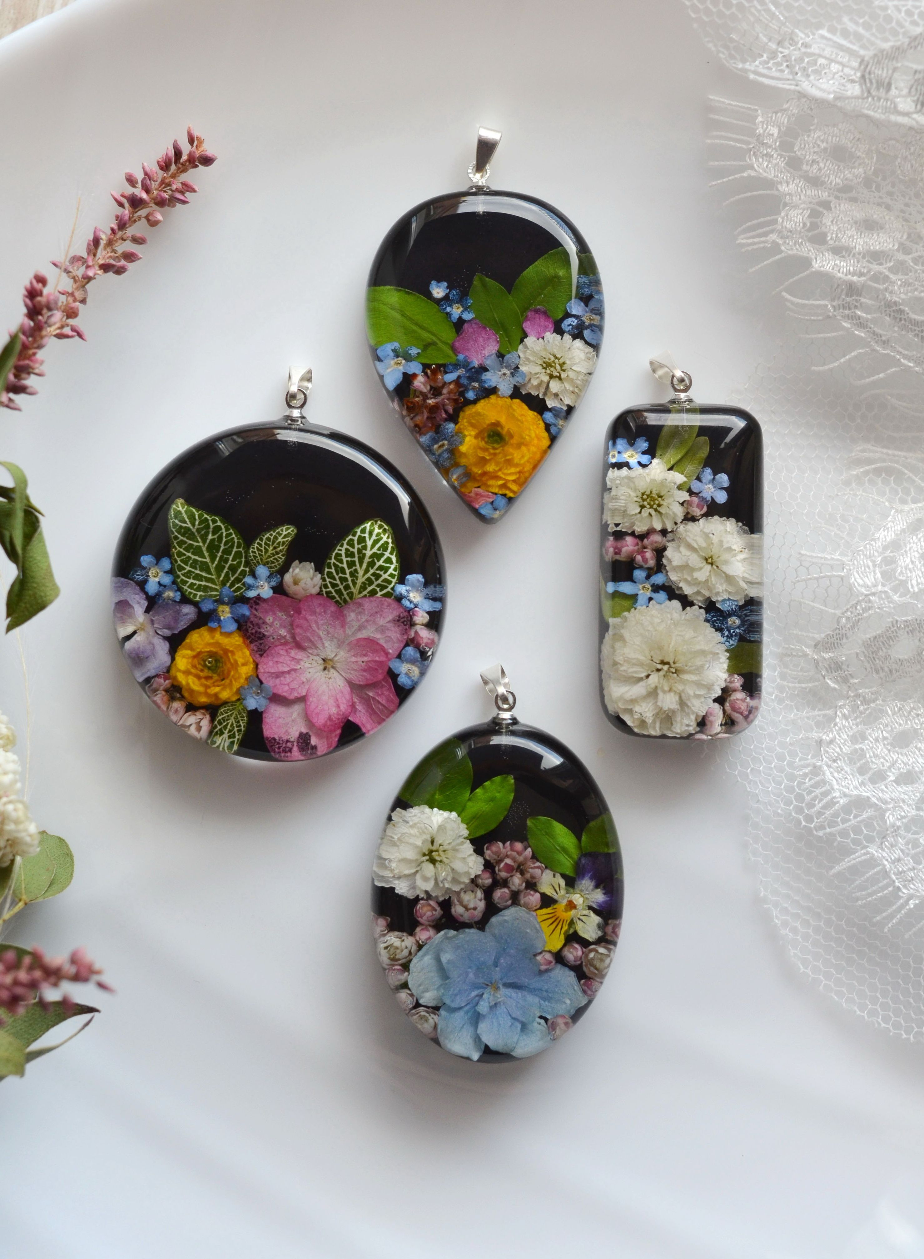 Photo of Pendant with pansies and hydrangea in resin. Necklace with real flowers on a black background.