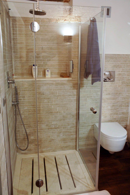 Piatto doccia a doghe in travertino in un bagno con mosaico ...