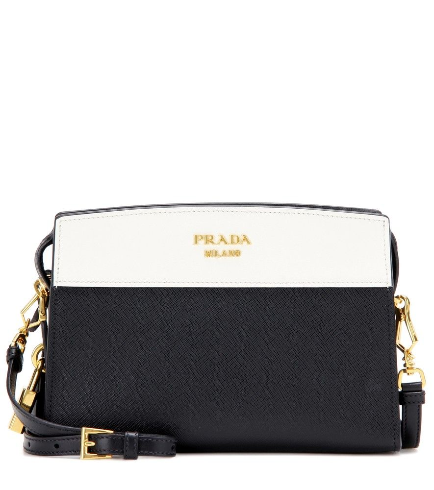 Prada - Esplanade leather shoulder bag - Prada's Esplanade shoulder bag is a compact classic. Adorned with gold-plated hardware for luxe elevation, this piece comes crafted from panels of smooth white leather and textured black Saffiano leather for cool contrast. The brand's padlock charm gleams to one side, adding charming detail. Take yours into the evening as a chic clutch, or attach the shoulder strap to go hands-free. seen @ www.mytheresa.com