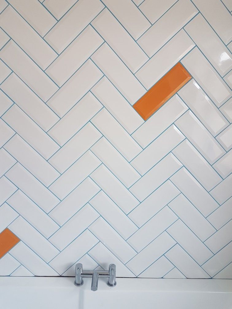 White Metro Tiles In A Herringbone Pattern With Blue Grout And A
