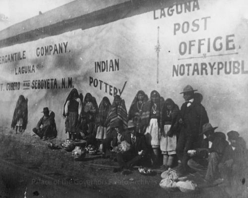 Women from Laguna Pueblo selling pottery outside Post Office building at railroad station, Laguna, New Mexico Date: 1905? Negative Number 044830