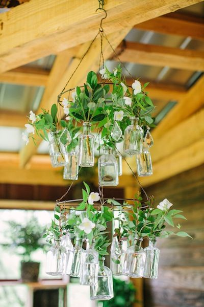 Clippings of greenery look great in a chandelier made of vintage, glass bottles.