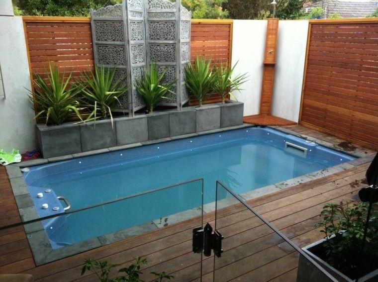 valla de madera alta y piscina en el jardn pequeo