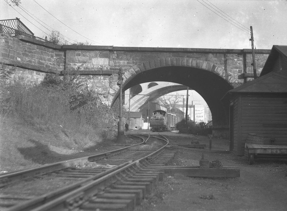 This is the Baltimore & Ohio's branch into Georgetown, Washington, DC ca. 1935. The old stone bridge is actually a former Aqueduct of the C Canal from Georgetown to Virginia. The newer bridge with the train under it is the Francis Scott Key Memorial Bridge which is still in use today.