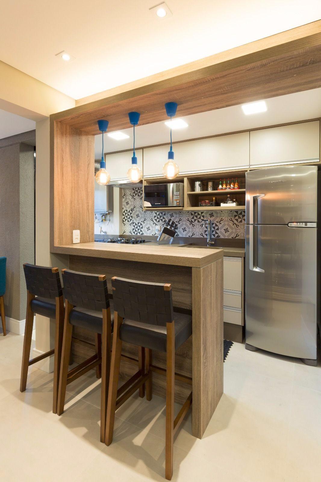 Balcão de madeira que divide a cozinha da sala com iluminação ...