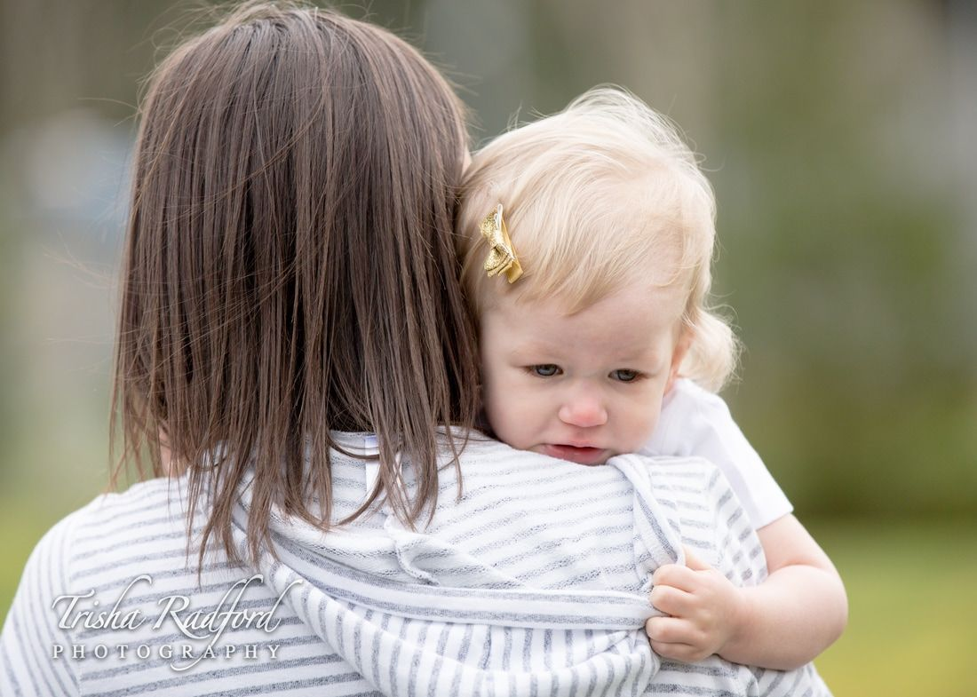 Photo of an upset two year old girl holding on tightly to her mommy