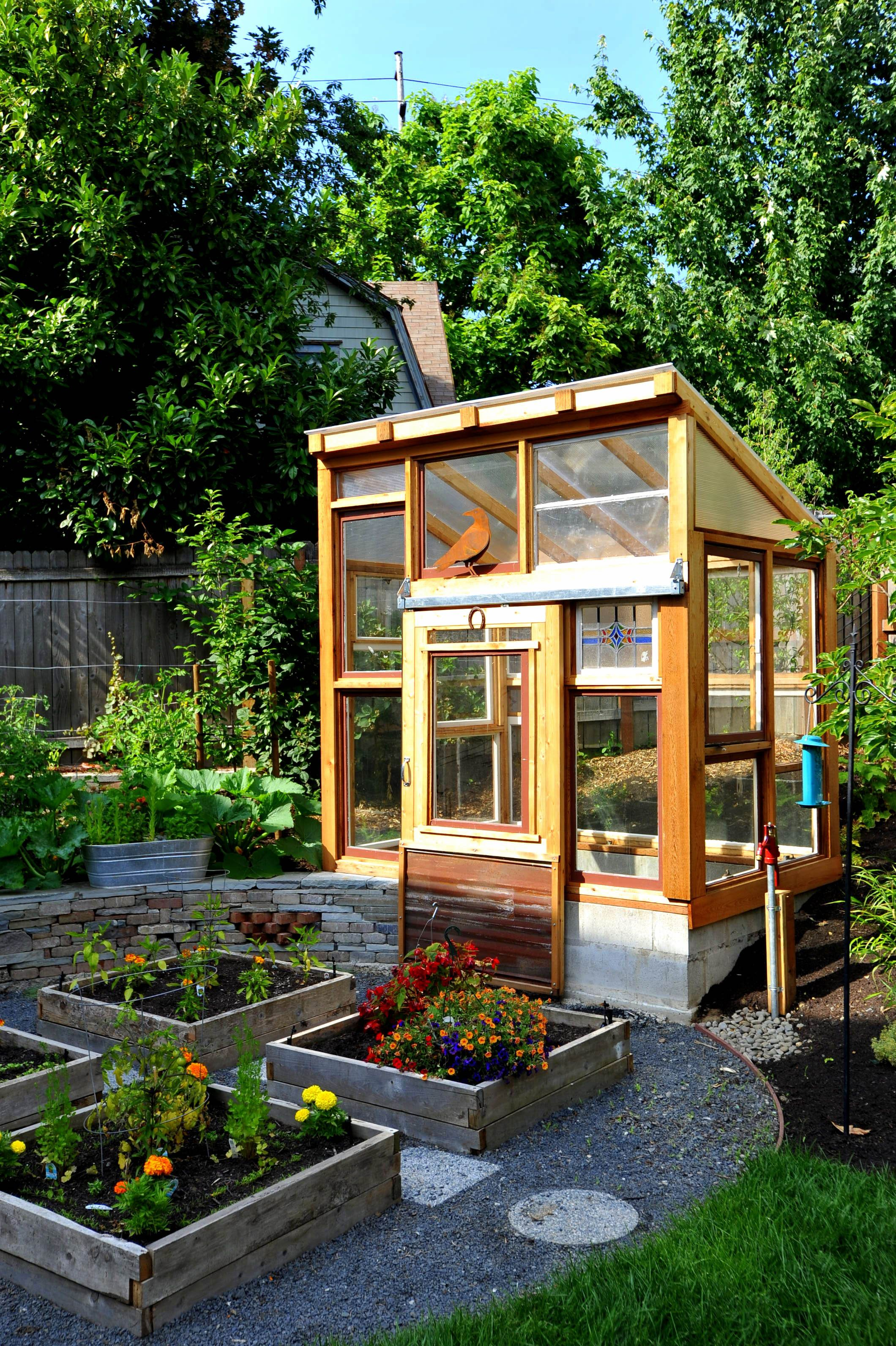 greenhouse and raised bed vegetable garden surrounded by perennial