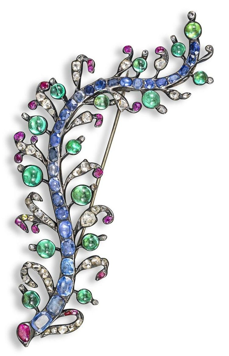 An 18th century gem-set foliate brooch. The centre stem is set with graduated cushion-shaped sapphires. The leaves with cabochon emeralds, rubies and rose cut diamonds. Closed back silver mount. 11cm. #antique #brooch