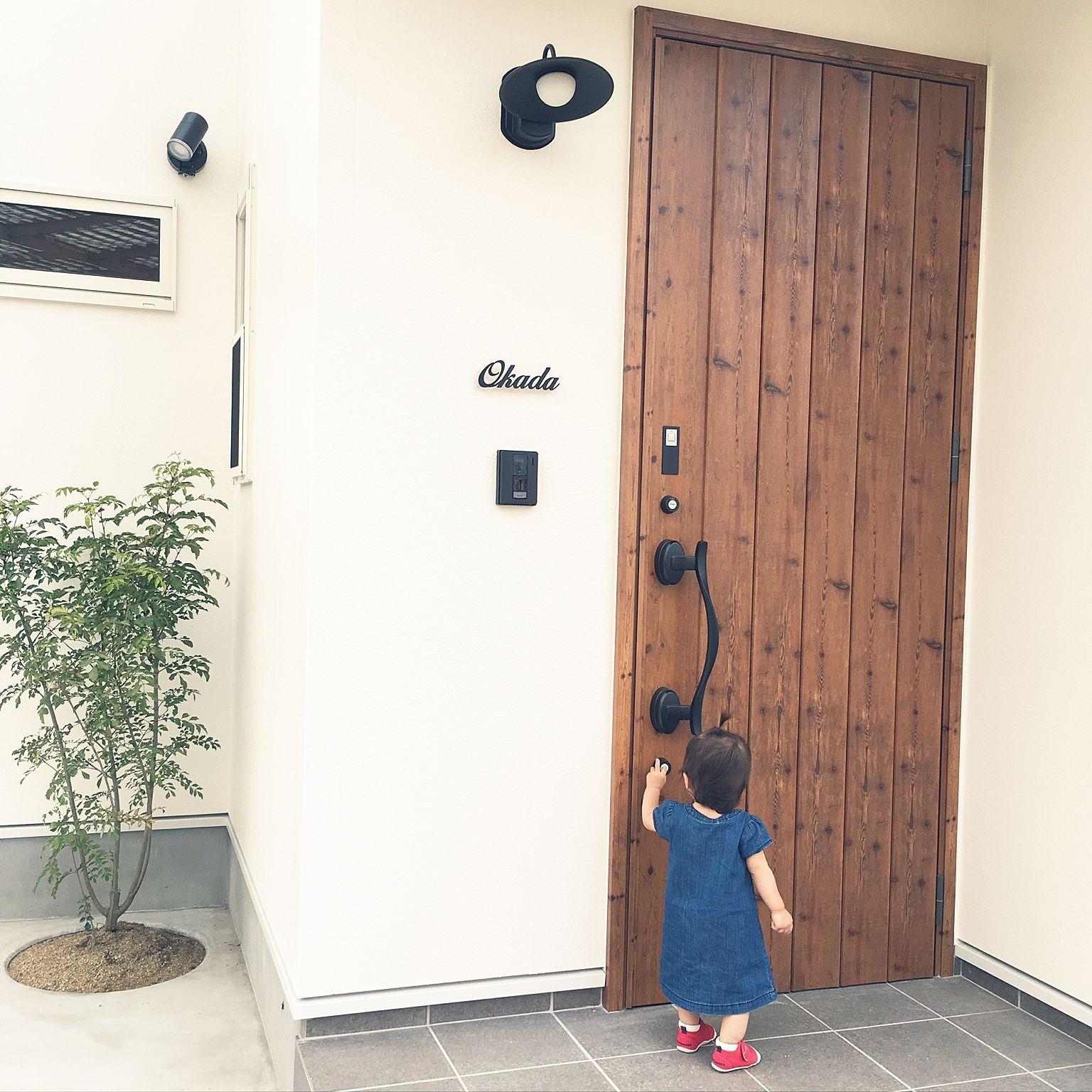 玄関 入り口 こどもと暮らす 塗り壁 白い家 外灯 などのインテリア