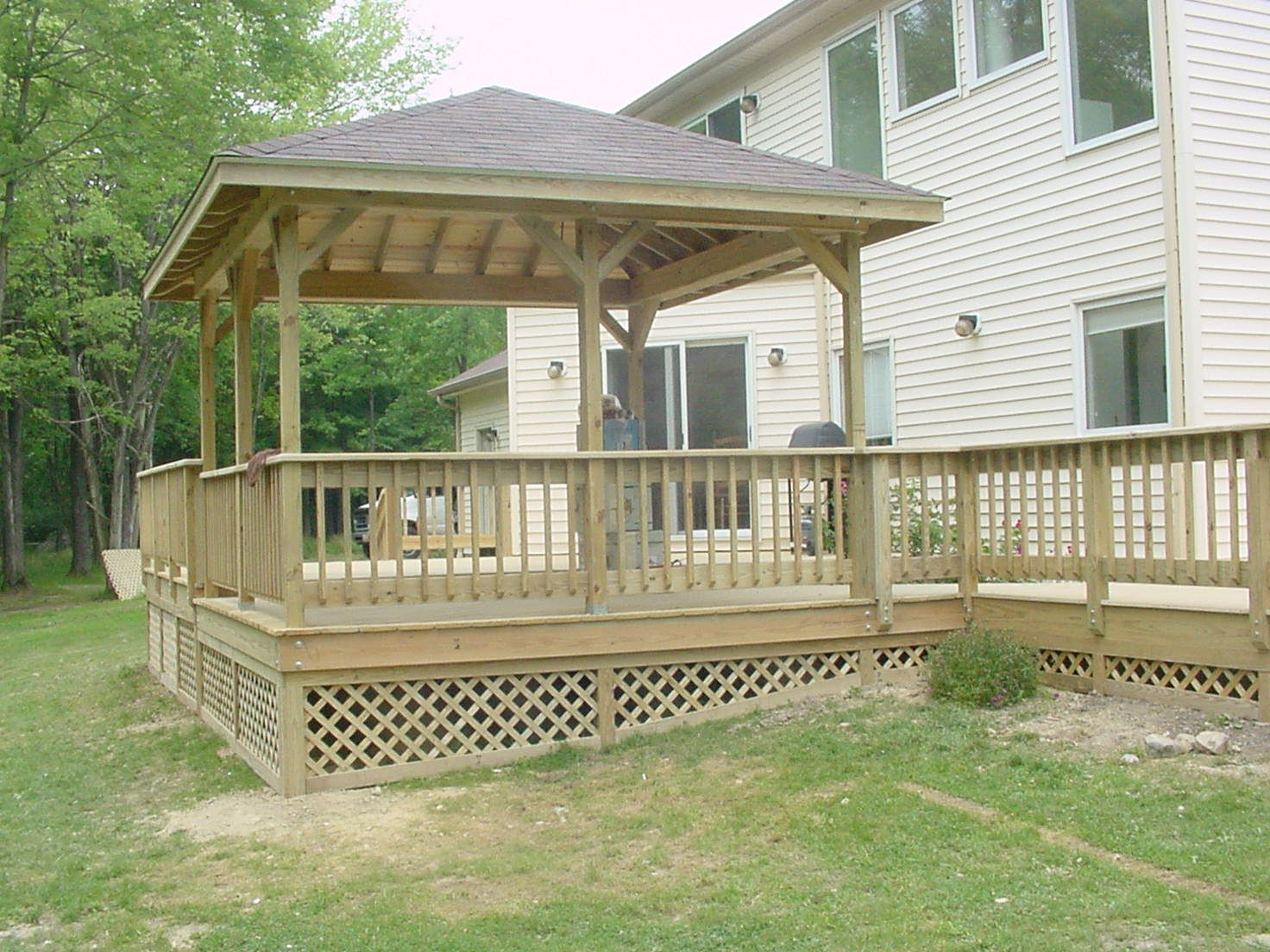 Lattice Wood Deck Along With White Wood Siding And Wooden Deck Railing