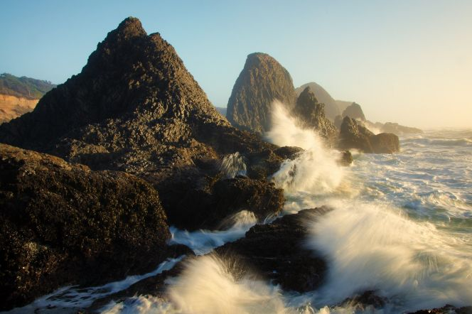 Waves crash onto tall rocks along the Oregon coast with the sun shining down in the distance.