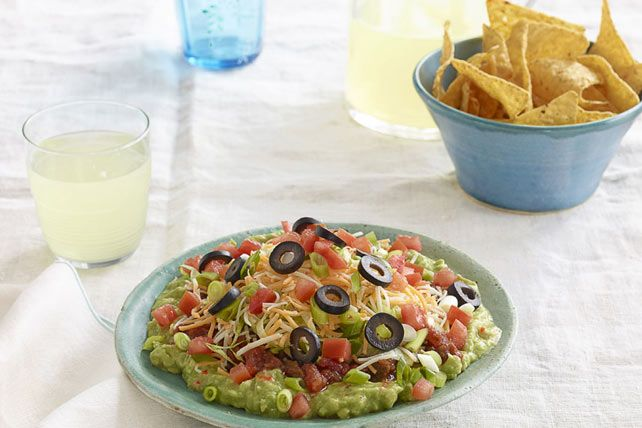 Start with lime-spiked guacamole, then layer with fresh summer ingredients and shredded cheese.  This easy dip is a crowd-pleasing appetizer.