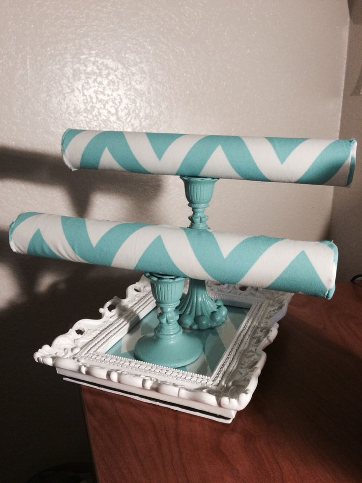 DIY watch/bracelet holder using: • a picture frame as the base  • fabric  • candle sticks  • paint & mod podge (or use spray paint) • glue gun  • foam sheets to wrap the  • foam rods (or you can use pvc pipes or cardboard rolls)