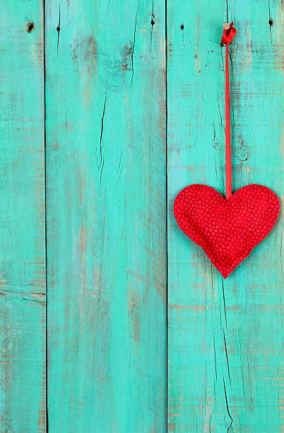 red heart hanging on teal blue wood background