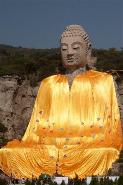 El Buda de Mengshan cubierto con el manto de oro en la provincia de Shanxi, China.  El Buda de Mengshan es la más antigua estatua de Buda tallada en piedra de China y se ha dado una bata gigante para cubrir y proteger su cuerpo se desmorona.  El 1500-años de edad, estatua 206ft se le dio un lavado de cara 4m EUR año pasado, pero los fondos no podía estirarse para cubrir reparaciones de carrocerías.