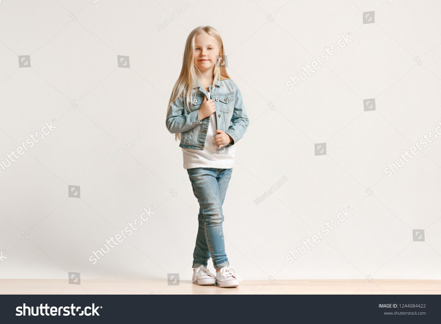 0948a0160 Full length portrait of cute little kid girl in stylish jeans clothes  looking at camera and