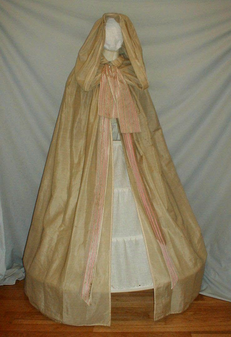 Romantic Era Hooded Cape A rare 1850-1860 beige pumpkin hooded full length cape. The cape is made of a silk and wool blend fabric. The cape has a ruffled collar. The large hood drapes over the shoulder when not worn. It is pleated at the back with a center button. The neckline has a pink and white stripe ribbon with long streamers that extend to the edge of the hemline. The cape has a hook and eye closure near the neckline.